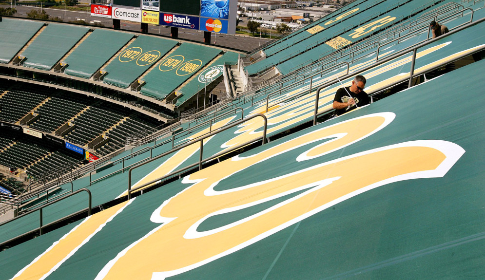 Mike Lawson affixes a green tarp over upper deck seats at McAfee Coliseum Wednesday, March 15, 2006, in Oakland, Calif. (AP Photo/Ben Margot)